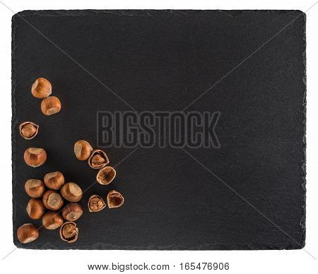Hazelnuts on a black slate board. Isolated on white background. Top view.