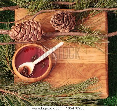 Jam of pine cones on a wooden texture with pine cones, branches. template for advertising eco store. In wooden dishes with jam, a wooden spoon.