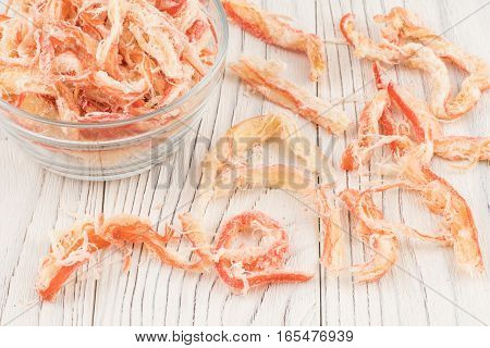 Dried squid in a glass bowl on old wooden table. Selective focus.