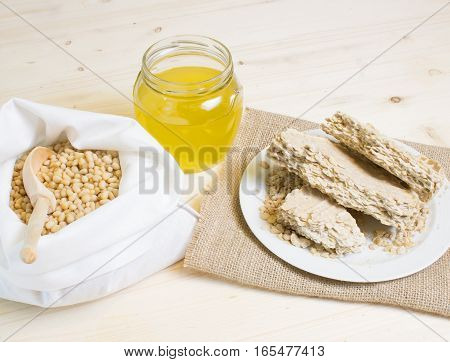Food for vegans. The pine nuts in a white cotton bag, cedar oil is cold pressed and a cake of pine seeds on a wooden vintage texture. Template for your advertising.