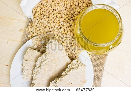 Food for vegans. The pine nuts in a white cotton bag, cedar oil is cold pressed and a cake of pine seeds on a wooden vintage texture. The view from the top. Delicacies from Siberia