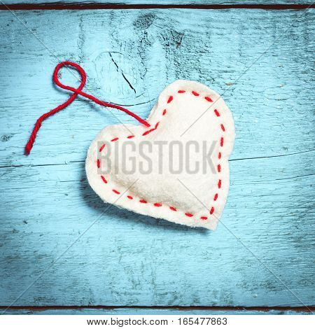 Valentine's Day. Colorful knitted hearts. White heart on the light blue boards. Valentines day. Heart pendant. Red heart. Valentine cards. Space for text. Toning in bright colors.