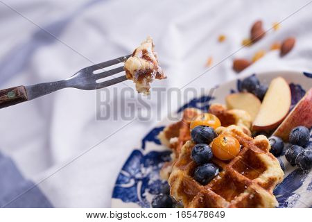 Closeup of a fork cutting through a blueberry waffle decorated with fresh blueberry in a nice dish.