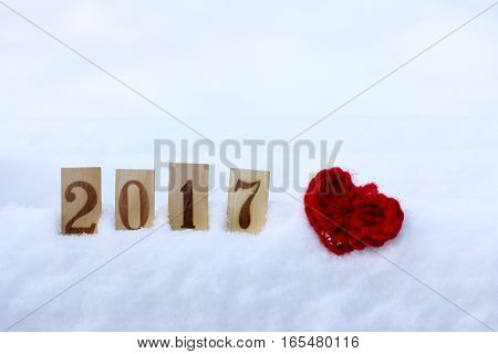 soft manually knitted heart symbol and wooden numbers on a background of a winter landscape / day enamored 2017