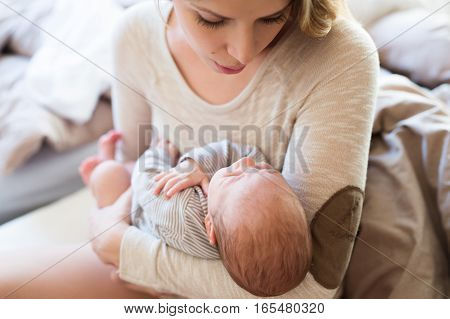 Beautiful young mother holding her baby son in her arms