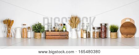 Kitchen shelf with various herbs spices utensils on white background