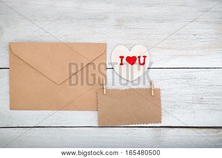 Valentine. envelope kraft paper and white wooden heart on a wooden background. View from above