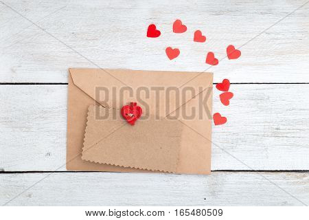 Valentine. envelope kraft paper and red hearts on a wooden background.