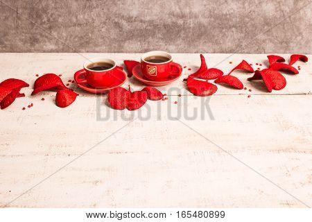 Two red coffee cups, petals in the shape of hearts on a white wooden background