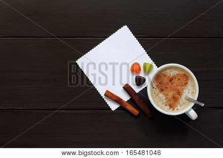 frothy cappuccino with heart symbol and colorful candies top view / sweet and beloved coffee