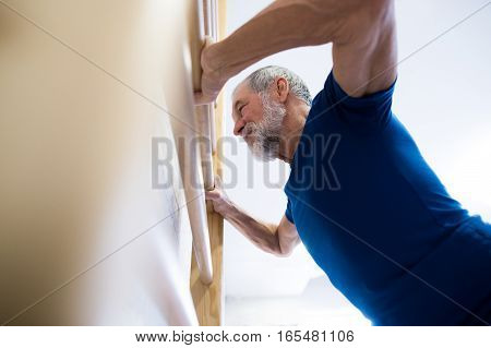 Senior man in sports clothing exercising on wall bars