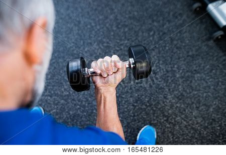 Unrecognizable senior man in sports clothing in gym working out with weights.