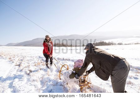 Father pushing daughter on sledge, mother pulling her. Beautiful family in sunny winter nature.