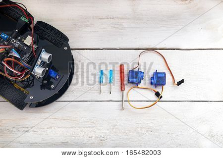 robotics parts and elements Servo screwdriver lying on a wooden table. view from above