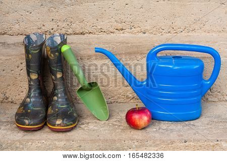 Gardening Tool (Rubber Boots Shovel Watering Can) And Red Apple On Concrete Steps Outdoor Close Up.