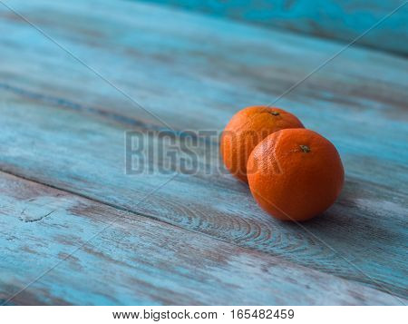 Fresh organic tangerine on old wooden table, side view.