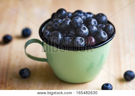 Fresh Blueberries in a retro cup on wooden board
