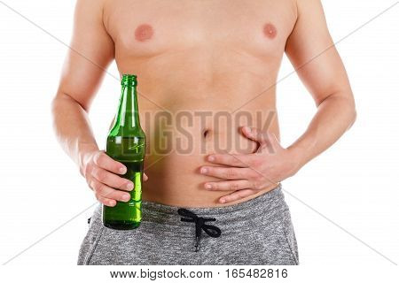 Close up picture of a young man's belly holding a beer