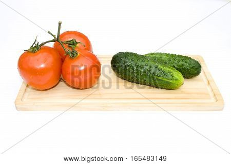Cucumbers and tomatoes disposed on piece of wood isolated on white