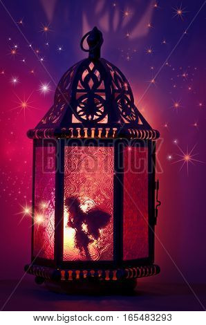 Fairy inside vintage metal lantern with layers of stars and purple and magenta colors in background/Fairy inside lantern with sparkling stars and purple and pink colors