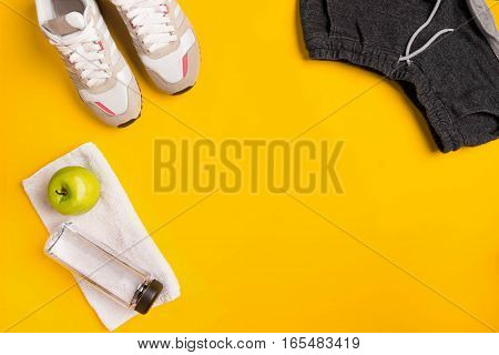 Athlete's set with female clothing and bottle of water on yellow background. Top view. Still life
