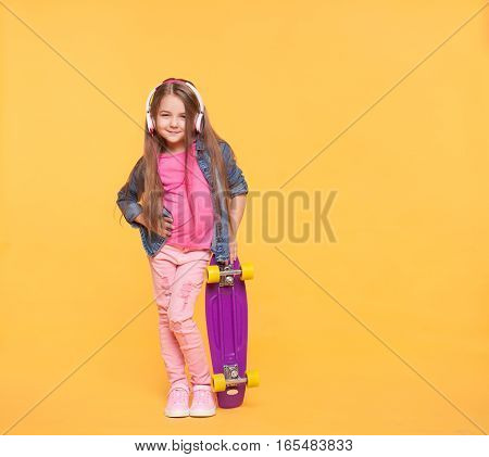 Stylish kid girl wearing vibrant modern clothes holding a skateboard over yellow background. Trendy little girl child listening to music in headphones. Full body size isolated portrait with copy space