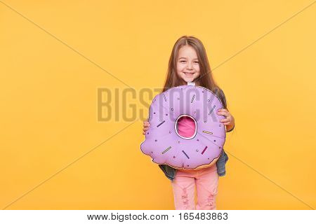 Little girl holding big donut over yellow background. Cute preschool kid smiling with giant null numeral isolated on vibrant color wall. Zero calories, Food and sweets concept
