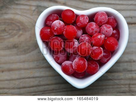 Frozen red viburnum berries in a white heart shaped bowl on old wooden background.Natural medicine,alternative treatment or health care concept.Selective focus.