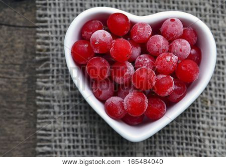 Frozen red viburnum berries in a white heart shaped bowl on sacking napkin background.Viburnum berries.Natural medicine,alternative treatment or health care concept.Selective focus.