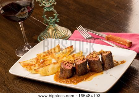 Close Up Of Forest Animal Steak With Potatoes And A Glass Of Wine