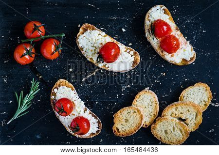 Roasted tomato and fresh ricotta cheese bruschetta on textured black background. Table top view
