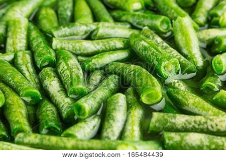 Wet fresh green french bean in water closeup as background. Healthy vitamin food.