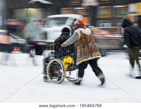 Woman Pushing Man In A Wheelchair