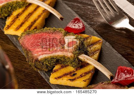 Close Up Of Lamb Chops With Toasted Bread And Red Onion On A Black Stone