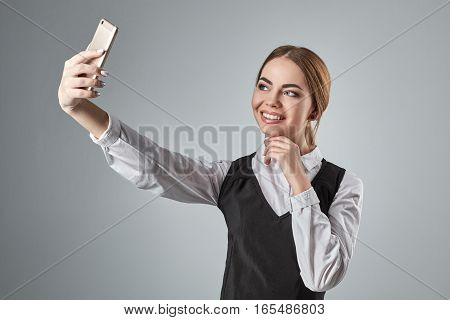 Portrait of young caucasian business woman in suit doing selfie on the phone. In studio on a gray background