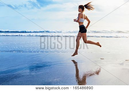 Active sporty woman runs along ocean surf by water to keep fit and healthy. Beach background with sun.