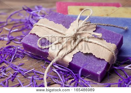 Collection of handmade, natural organic soap on wooden background. Spa products. Purple tinted