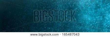 Glitter sparkling abstract blue bokeh defocused background, border design panoramic banner
