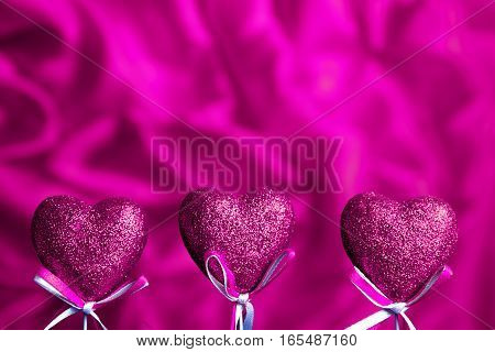 Valentines day. Pink hearts on pink blurred background closeup with copy space for congratulation
