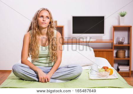 Young lonely woman is sitting in bed and thinking.