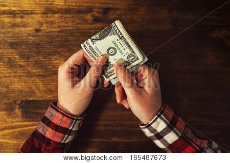 Woman paying with USA dollar money banknotes top view of female hands with folded stack of american cash