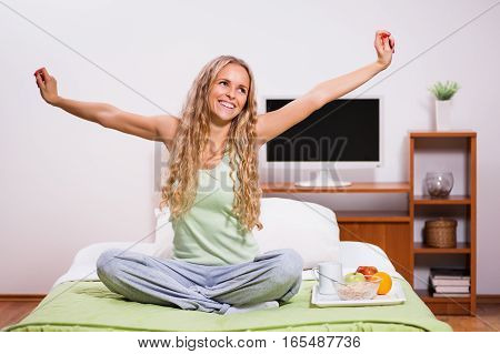 Young woman waking up in the morning. It's time for breakfast.