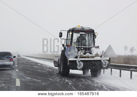Small snowplow with brushes rides on the route and removing snow