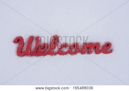Welcome message. Red wood sign in the snow