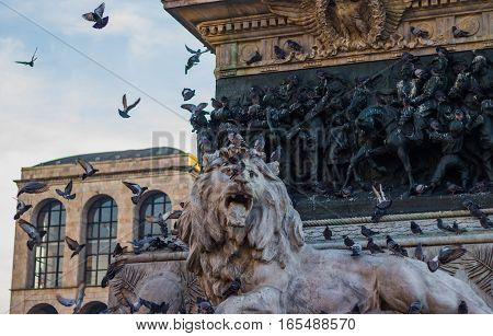 MILAN, ITALY - DECEMBER 09, 2016: Lion in Piazza del Duomo di Milano on a sunny day. Pigeons flying around