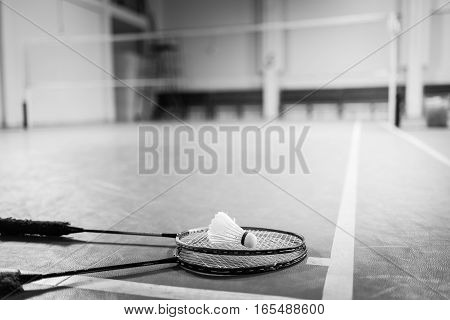Black and white. Badminton ball (shuttlecock) and racket on court floor. Badminton sports. Play badminton. Badminton exer cise. Badminton tournament. Badminton training. Badminton feather. Badminton health. Shuttle badminton.
