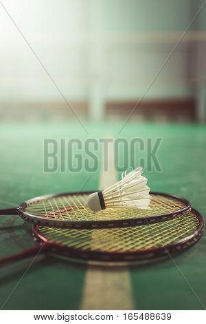 Badminton ball (shuttlecock) and racket on court floor. Badminton sports. Play badminton. Badminton exer cise. Badminton tournament. Badminton training. Badminton feather. Badminton health. Shuttle badminton. Badminton Vintage.