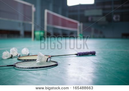 Badminton ball (shuttlecock) and racket on court floor. Badminton sports. Play badminton. Badminton exer cise. Badminton tournament. Badminton training. Badminton feather. Badminton health.