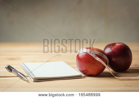 Apple, Tape Measure And Notepad  Lying On A Woode