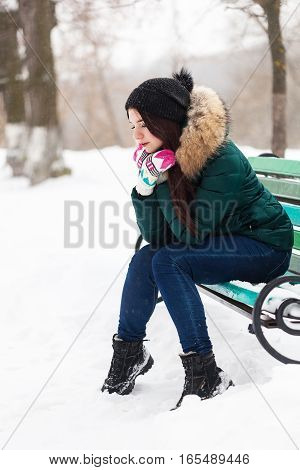 Portrait of a young girl in a winter park sitting on the bench
